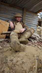 Encountering a resting soldier in under a shelter. Note the muddy boots and puttees