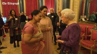 2-HM the Queen and holding a wine glass